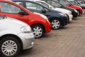 row of different european marques of used cars for retail sale on a motor dealers forecourt all logos removed